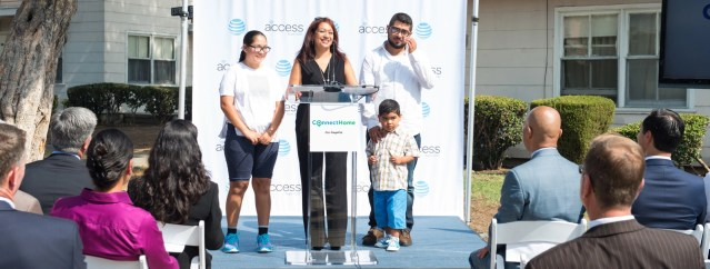connect home inclusion project, a mother, father, son and daughter at an event podium.