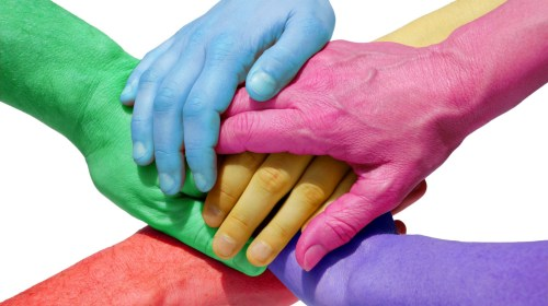Five hands painted in different colors in a hand huddle intended to symbolize inclusion for all.