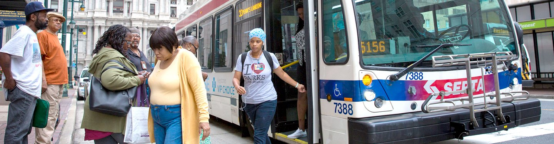 a black woman exiting a city bus