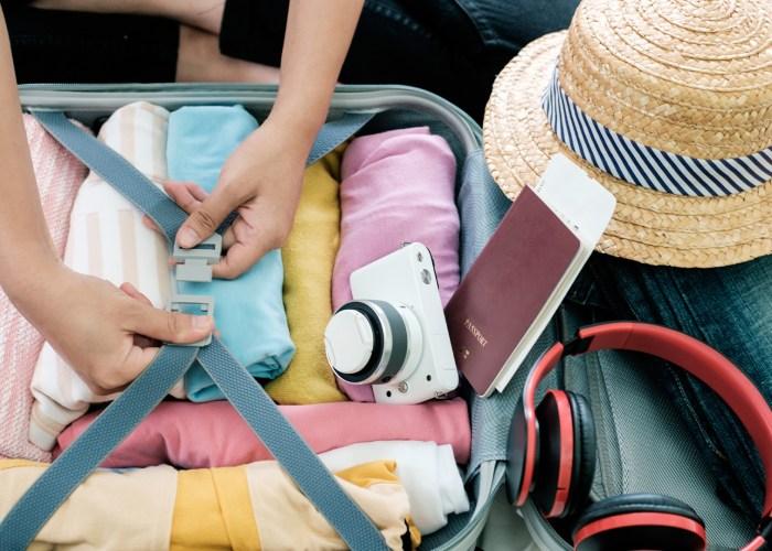 packing suitcase camera hat headphones
