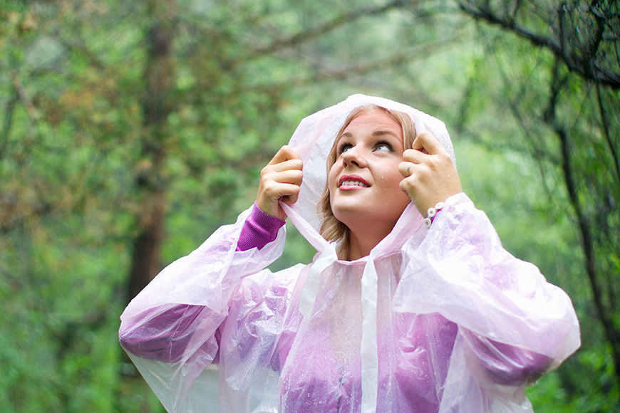 woman in plastic rain poncho forest looking up