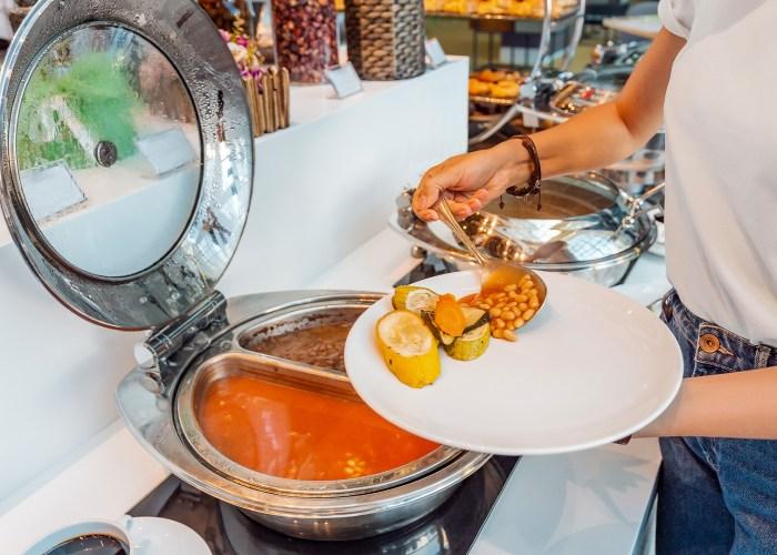Woman choosing food in open buffet at breakfast in hotel