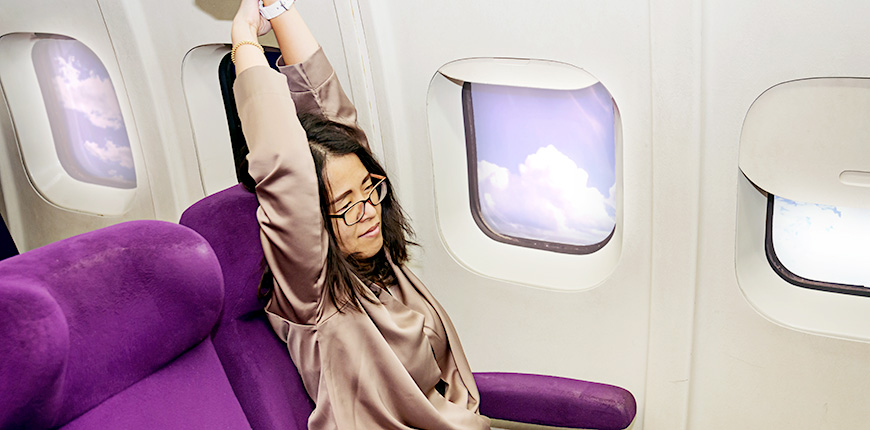 woman on a plane stretching arms up