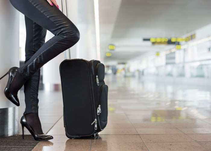 woman with high heels and suitcase in airport.