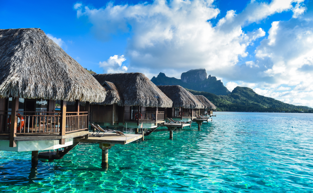 row of overwater bungalows in tahiti with mountain distance