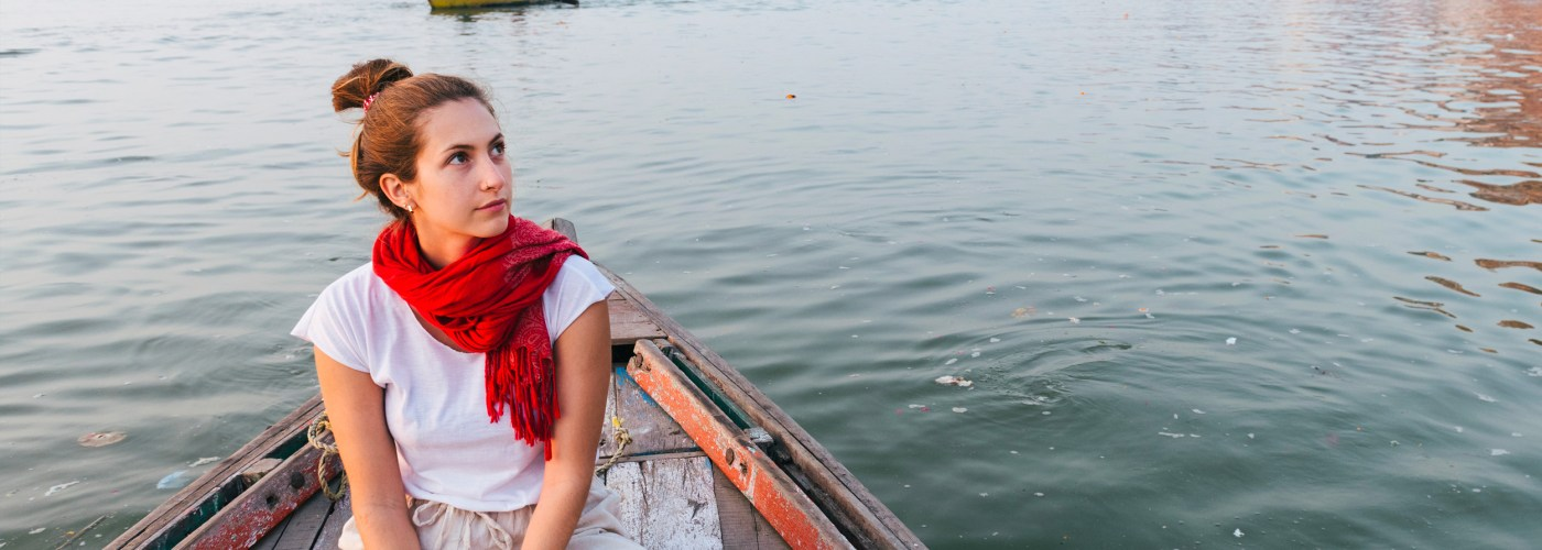 woman wearing scarf on a boat in the ganges river in India