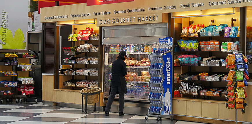 A woman arranges beverage displays inside at a gourmet market the airport