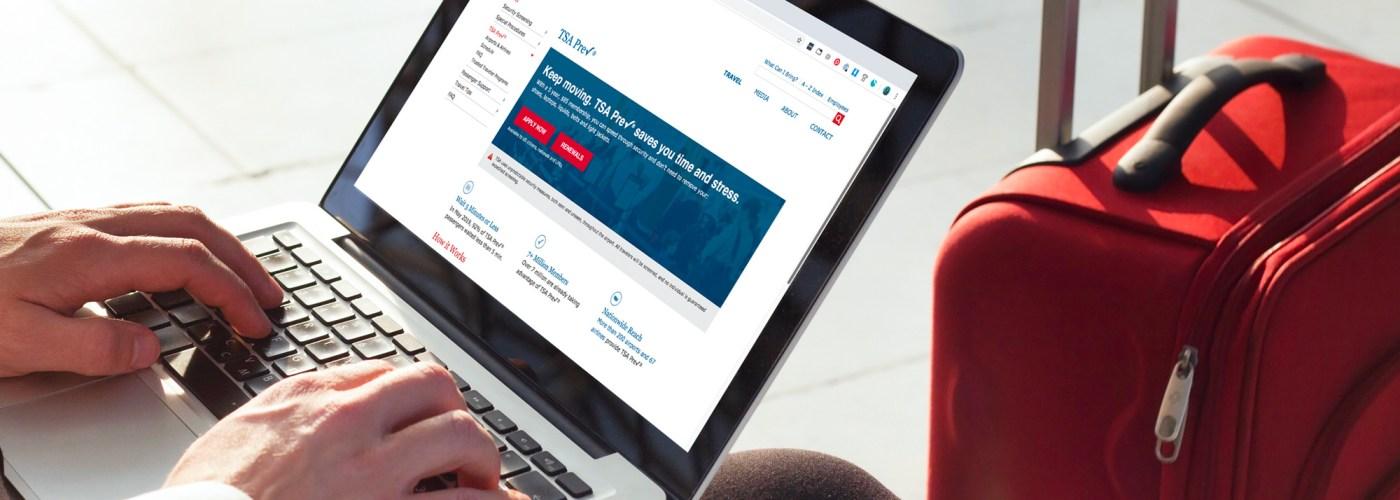 man check TSA Pre website laptop suitcase airport