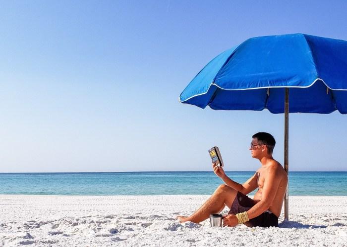Man reading a paperback book under a beach umbrella.