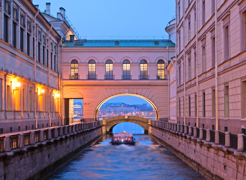 boat going through archway on canal in st. petersburg russia.