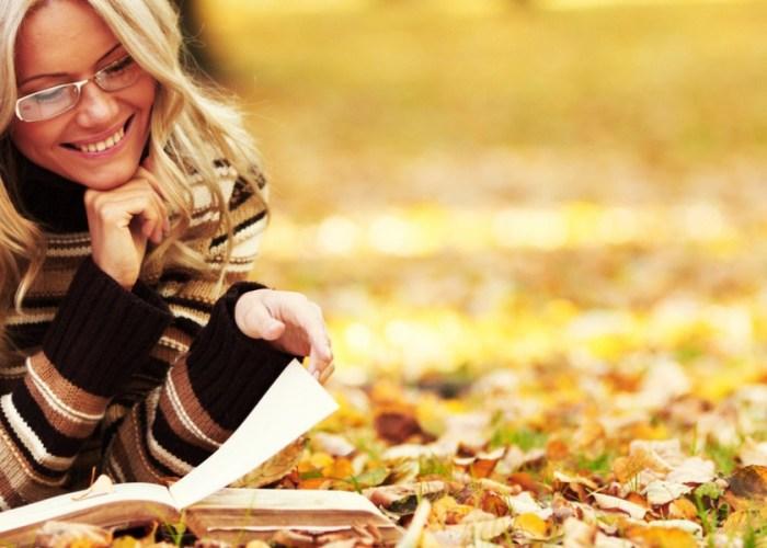 blonde woman reading a book in fall.
