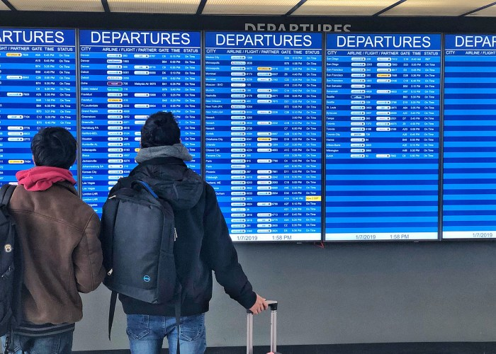 travelers in front of airport departure board