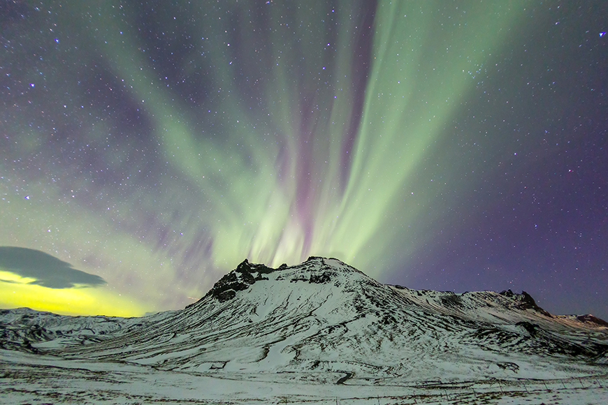 northern lights over mountain in iceland.