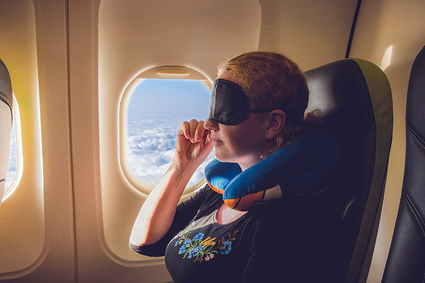 woman using traveling pillow and sleeping mask in plane