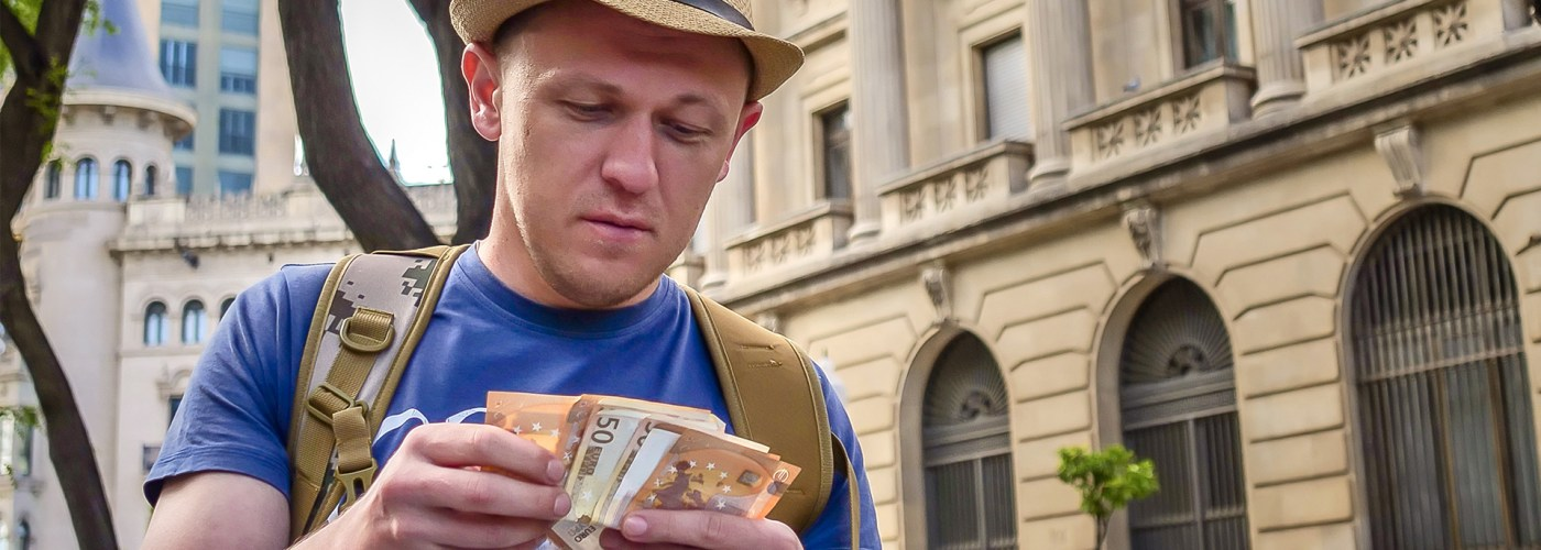 male tourist counts cash on the street of city