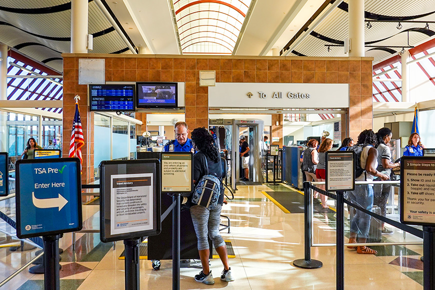 People going through TSA security screening a busy international airport.