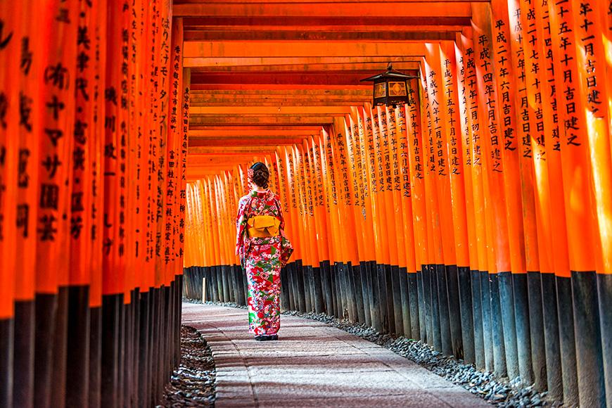 Women in kimono walking at Red Torii gates in Fushimi Inari shrine, one of famous landmarks in Kyoto, Japan