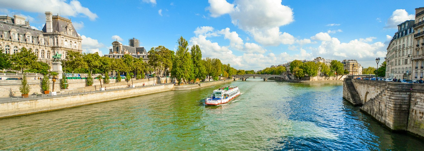 A cruise tourist boat floats down the Seine River near the Ile de la Cite in Paris, France