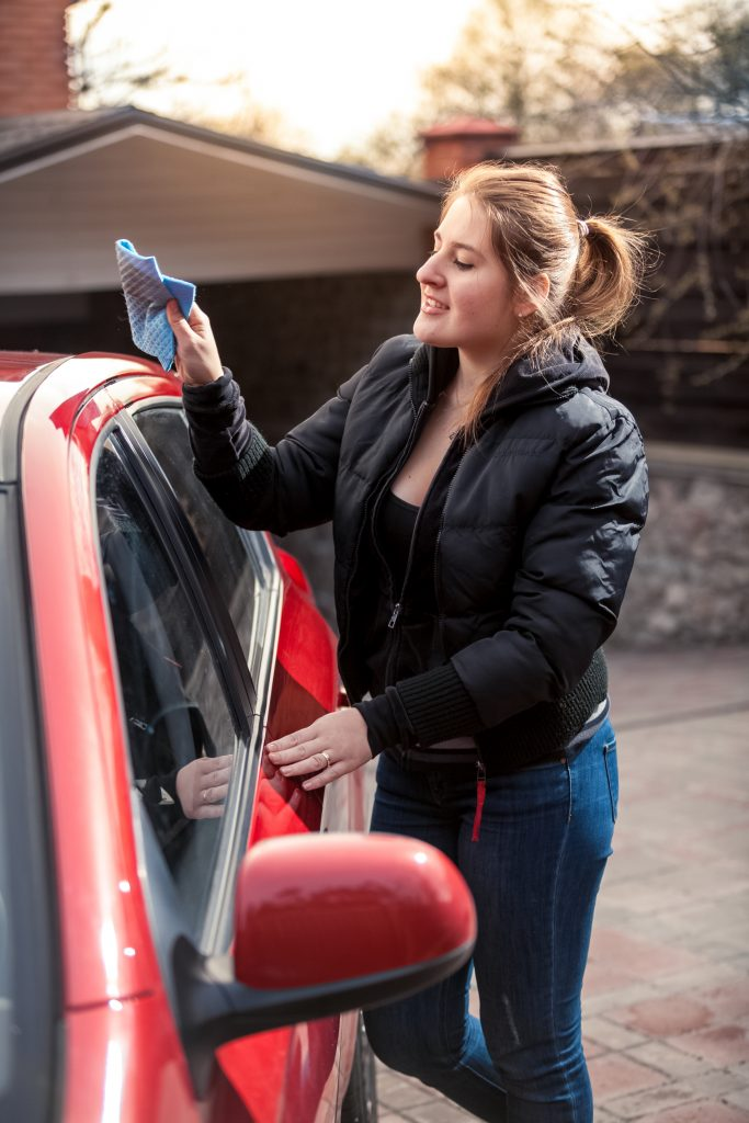 Woman washing her own car to save money