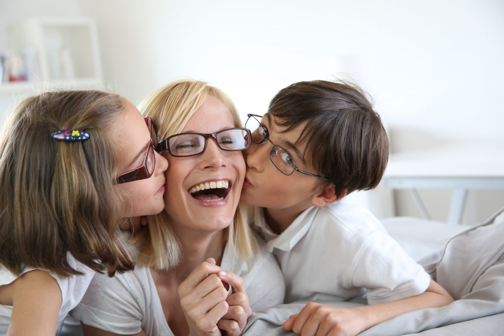 Kids kissing mom. All are wearing glasses.