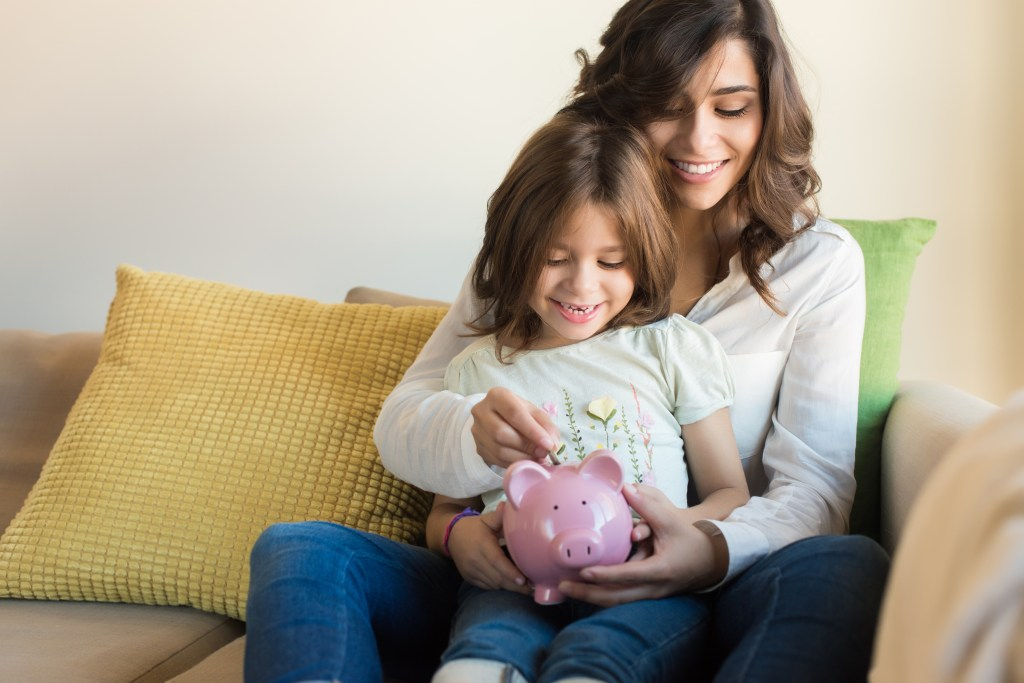 Mom and daughter saving money in a piggy bank