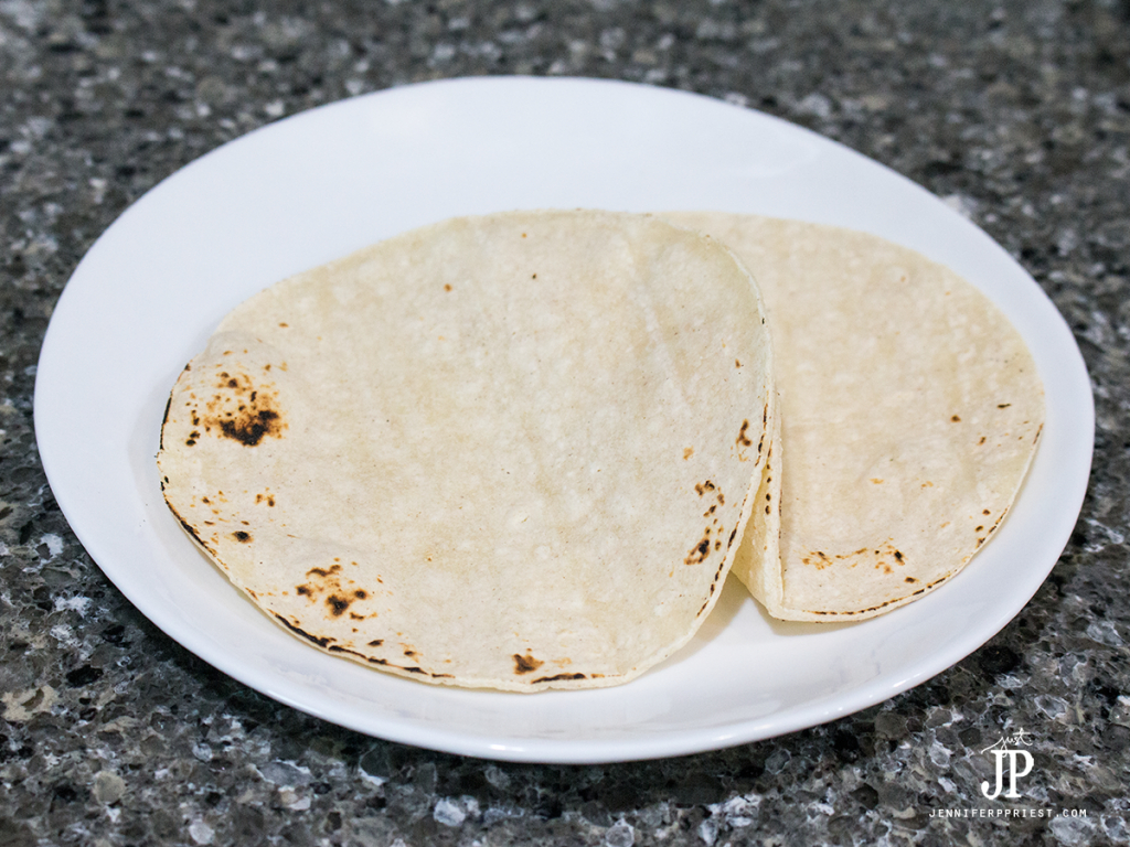 Warm tortillas over a gas flame to gently toast- use tongs to remove the tortilla safely. If you have an electric oven, you can grill the tortillas in a pan or heat them in the microwave. Heating them will make them pliable so we can bend them for the tacos.
