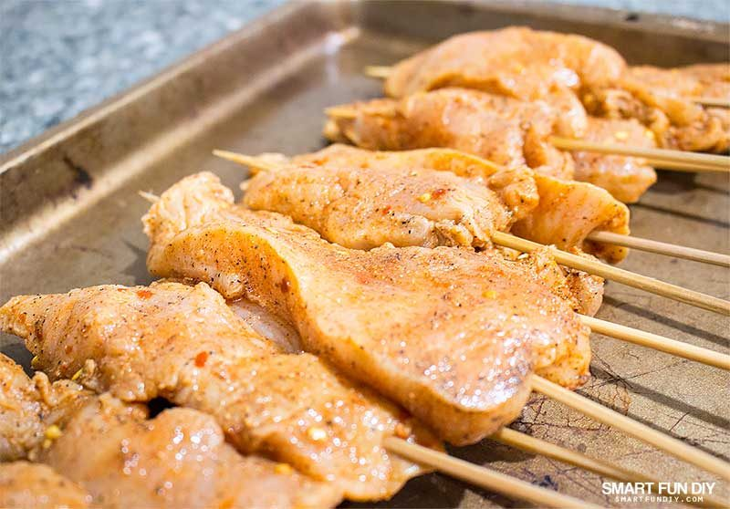 raw chicken skewers on pan
