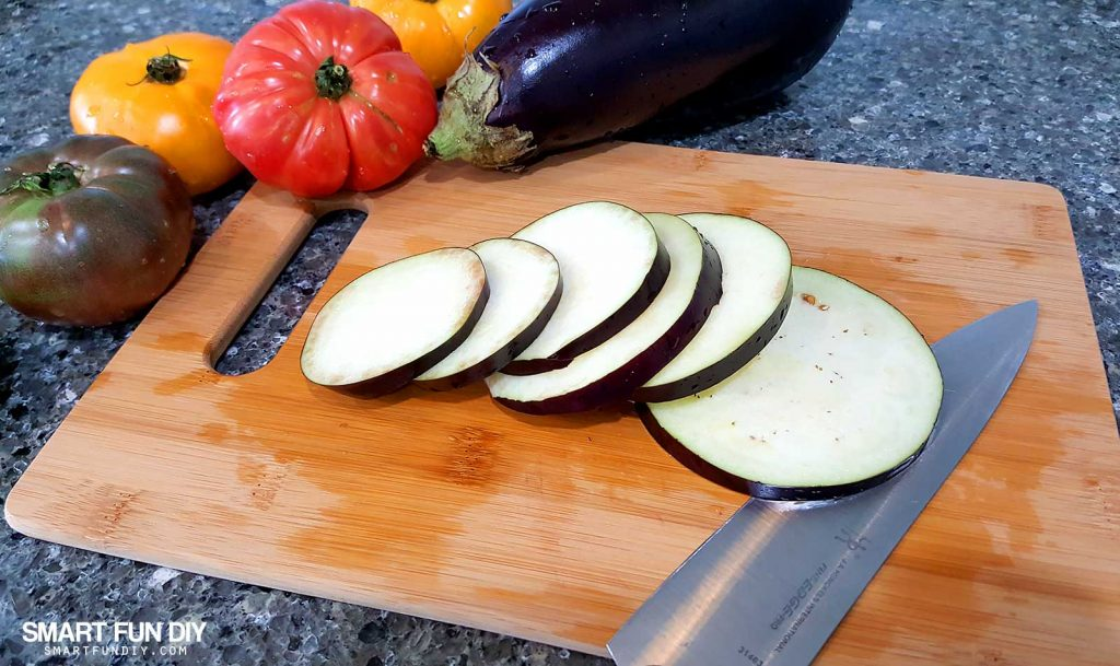 Slice eggplant to make a grilled eggplant and heirloom tomato salad recipe https://www.smartfundiy.com/mothers-day-lunch-grilled-eggplant/ #SoWorthIt