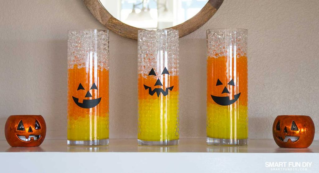 Candy Corn Vases with Jack-O-Lantern Faces! Halloween Decor is easy with GEMNIQUE Water Beads. See how to make this display for under $15!