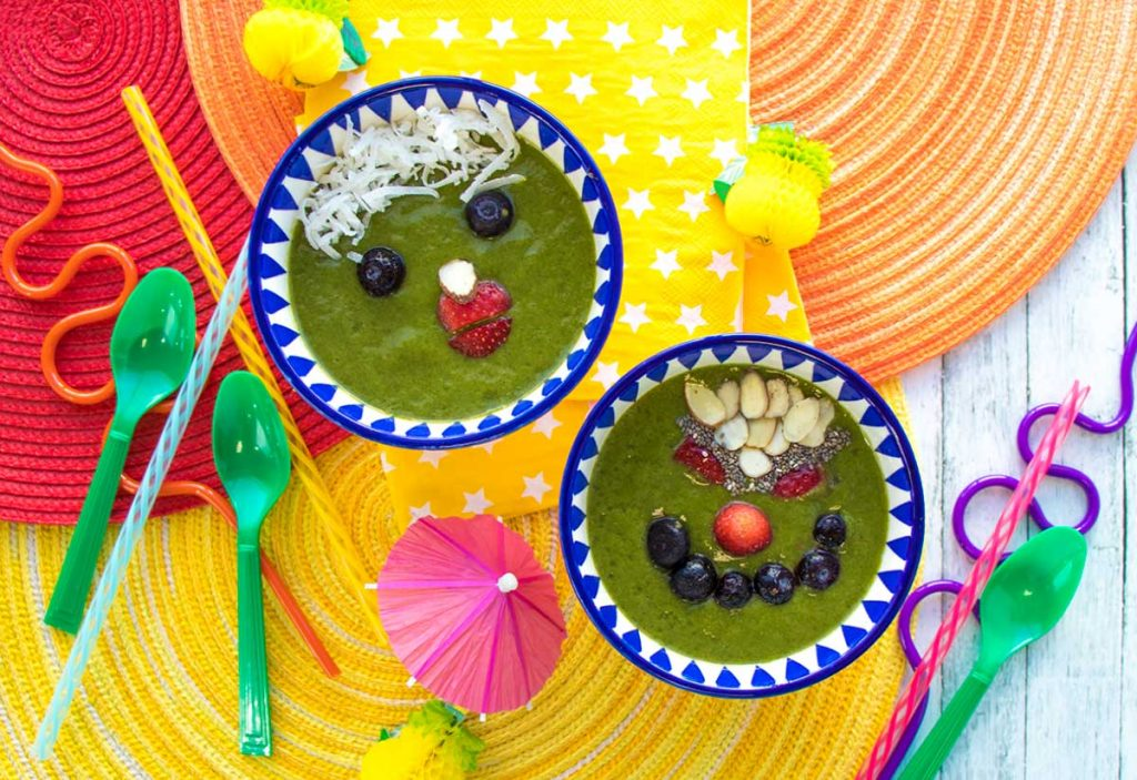 Kids Smoothie Bowls with funny faces made from fruit, nuts, and shredded coconut