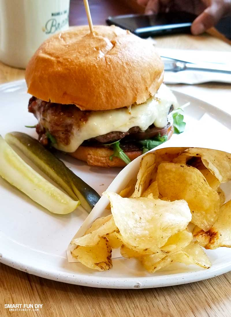 Gaines Brothers Burger with pickle spears and chips at Magnolia Table restaurant