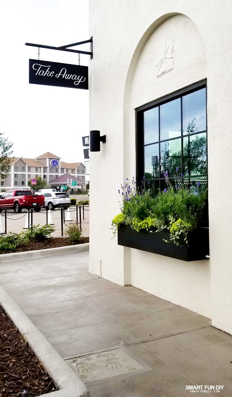 Flower Box and window at Magnolia Table restaurant with Chip and Joanna Gaines handprints in concrete