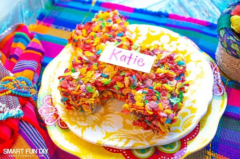 DIY pinata covered in Fruity Pebbles cereal used as dinner placecard