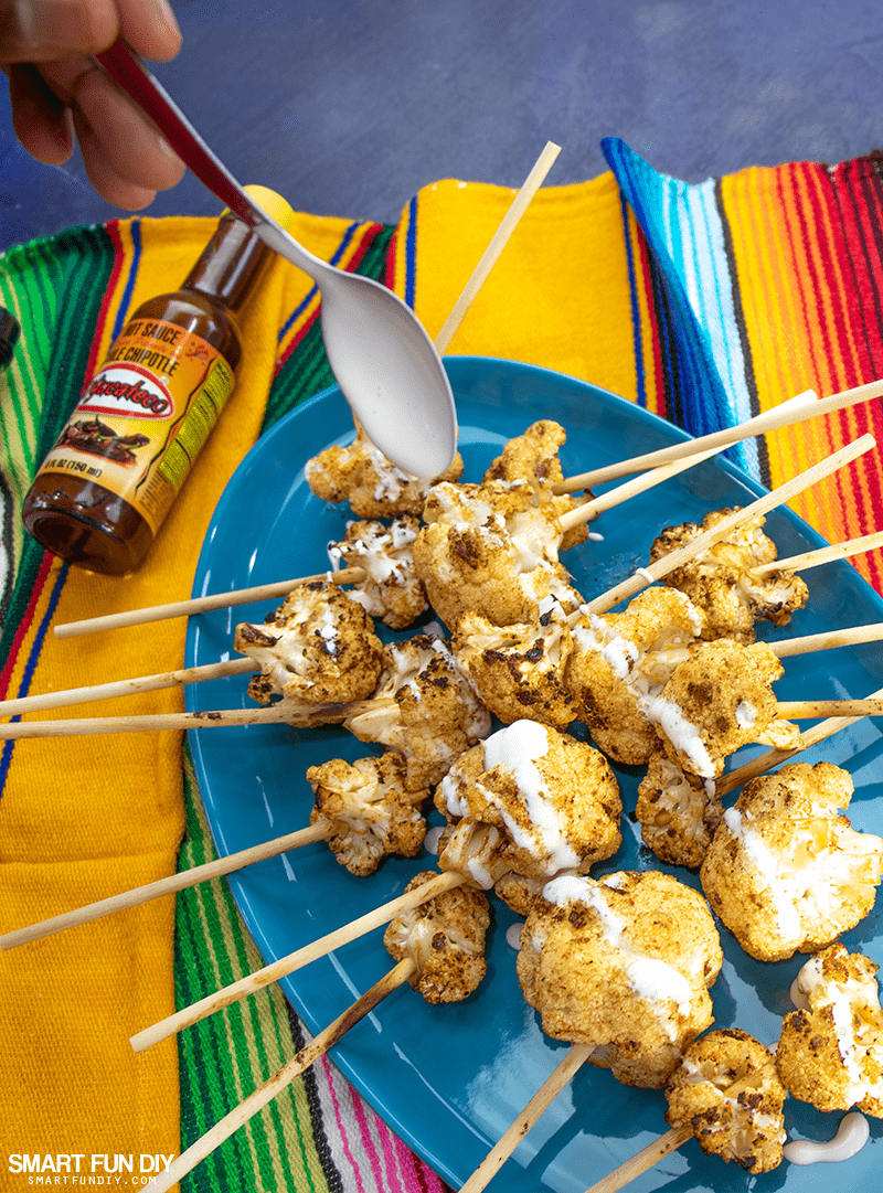 Drizzling crema Mexican or Mexican sour cream on the cooked cauliflower lollipops with a spoon