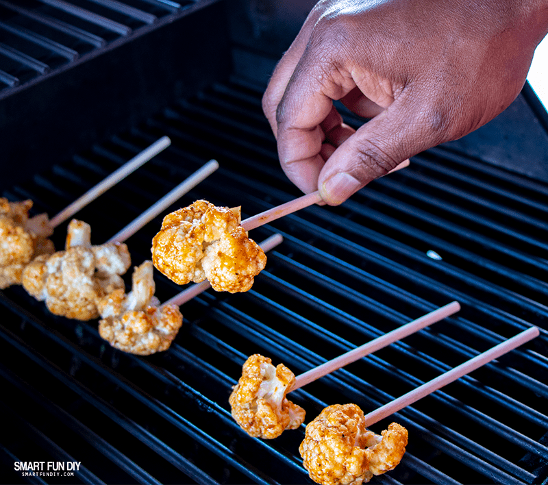 Placing cauliflower florets on hot grill for spicy cauliflower recipe