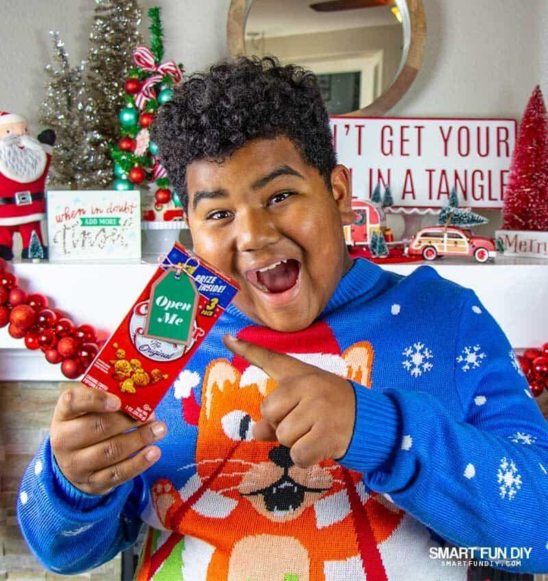 boy surprised at Cracker Jacks box with hidden cash gift inside