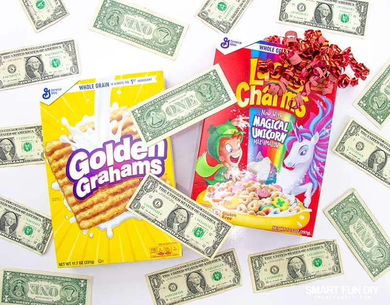 Golden Grahams and Lucky Charms cereal boxes with dollars on top