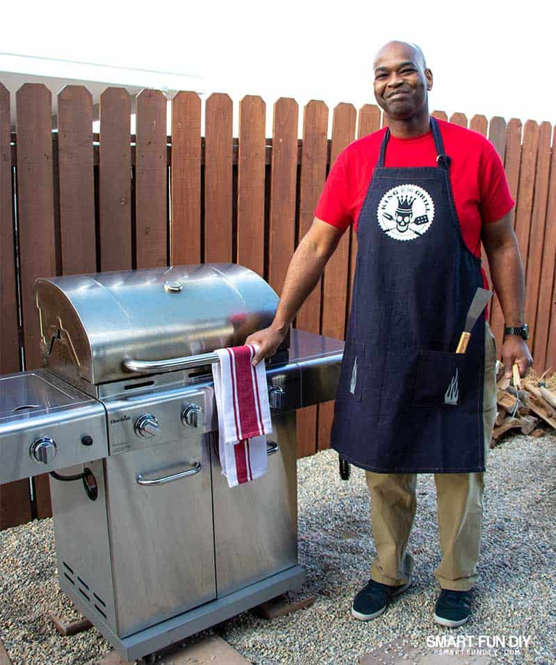 Man in red tshirt by grill wearing apron with King of the Grill Iron-on transfer made with Cricut Maker and Cricut EasyPress 2