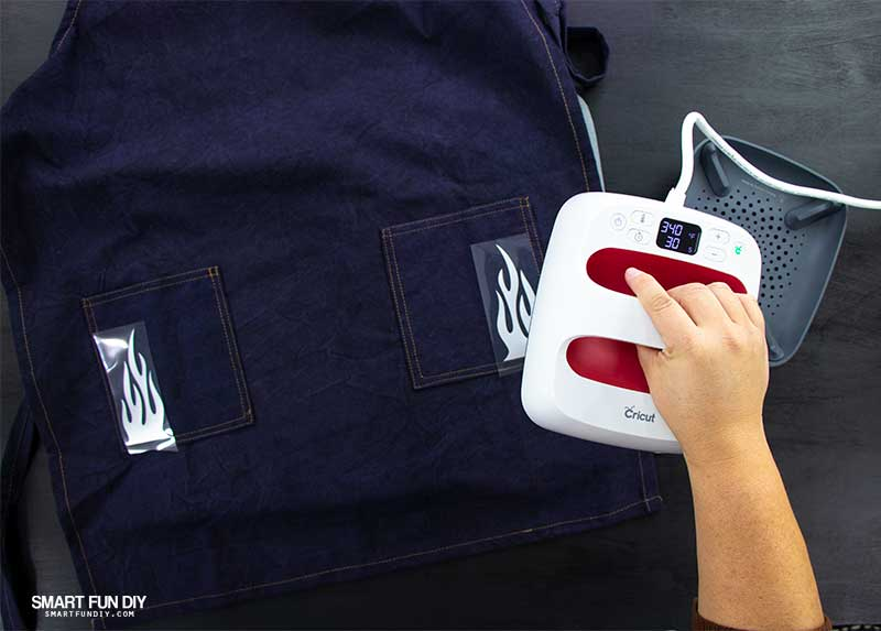 Cricut EasyPress 2 being used to iron on flames onto apron