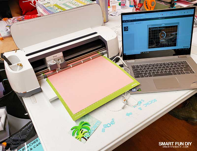 Cricut Maker and laptop on scrapbooking table at scrapbook crop