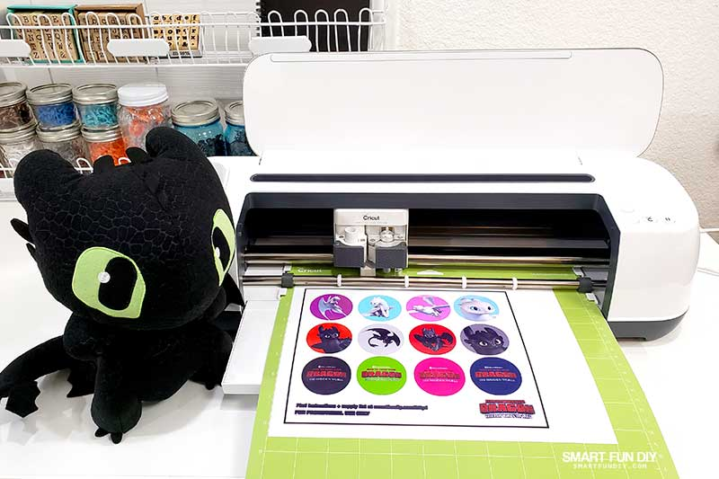 Toothless plush toy next to Cricut machine with mat loaded with How to Train Your Dragon printables sheet