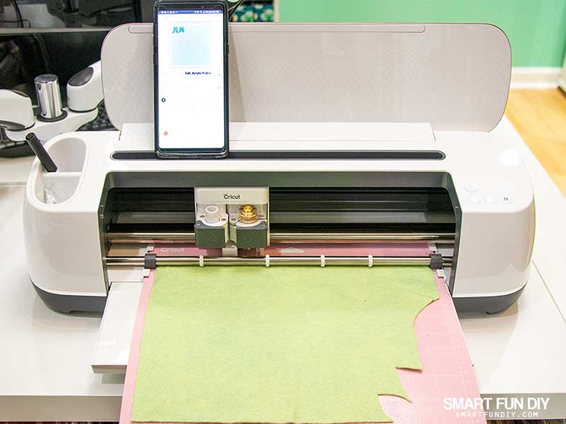 Cricut Maker cutting wool felt with android phone on top of the machine operating Cricut Design Space app