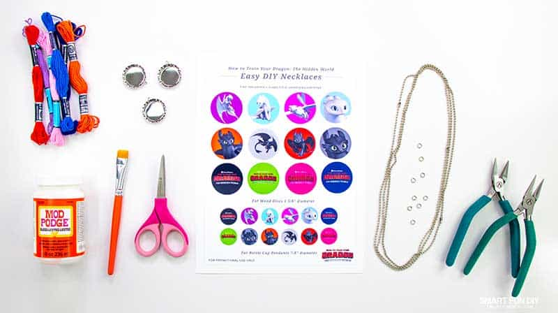 Flatlay of supplies to make bottlecap necklaces with printables from How to Train Your Dragon movie