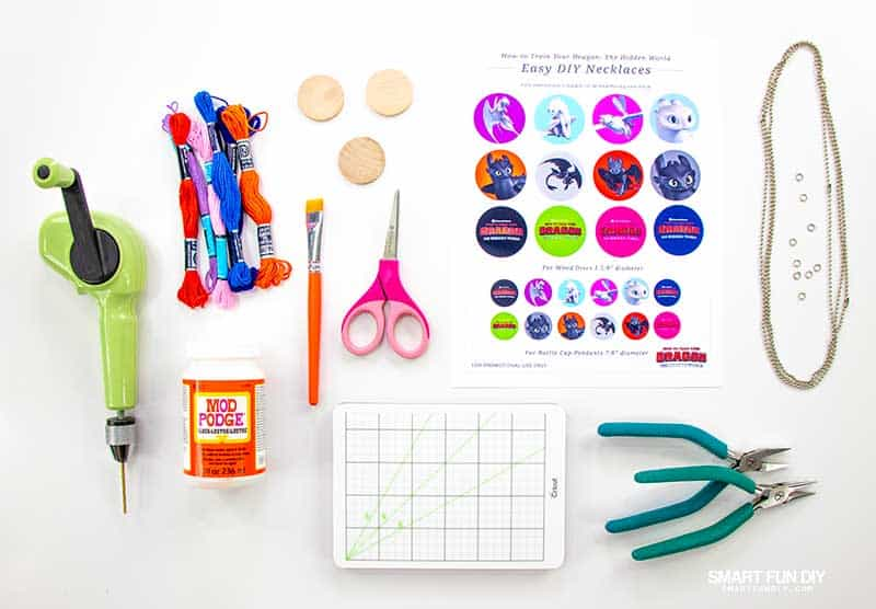 Flatlay of supplies to make wood disc necklaces with printables from How to Train Your Dragon movie