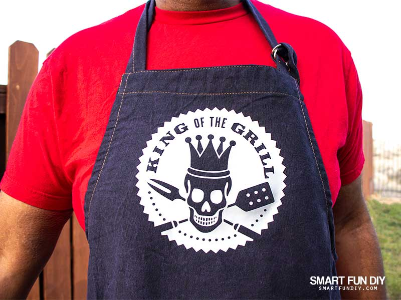 Man in red tshirt wearing apron with King of the Grill Iron-on transfer made with Cricut Maker and Cricut EasyPress 2