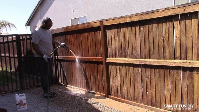 man rinsing Thompsons WaterSeal Fence Stripper from wood fence with hose