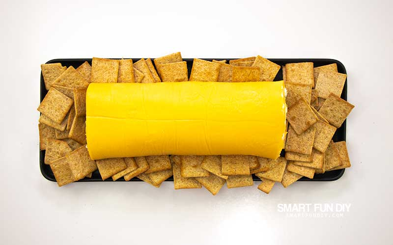 Velveeta Cheese Log on black plate surrounded by Wheat Thins crackers