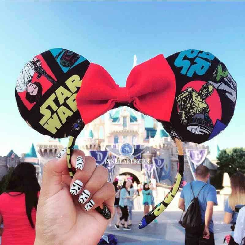 Handmade Star Wars Mickey ears being held in front of Sleeping Beauty castle in Disneyland