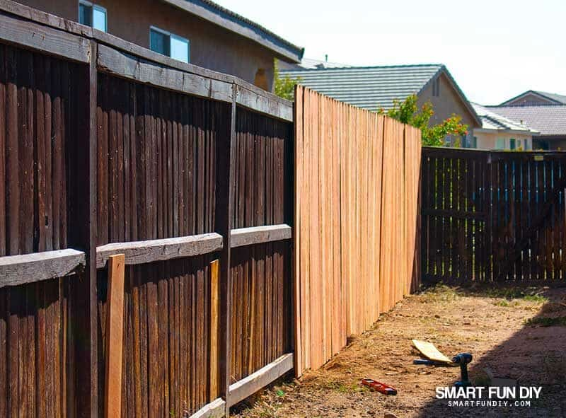Fence with broken slats and new slats