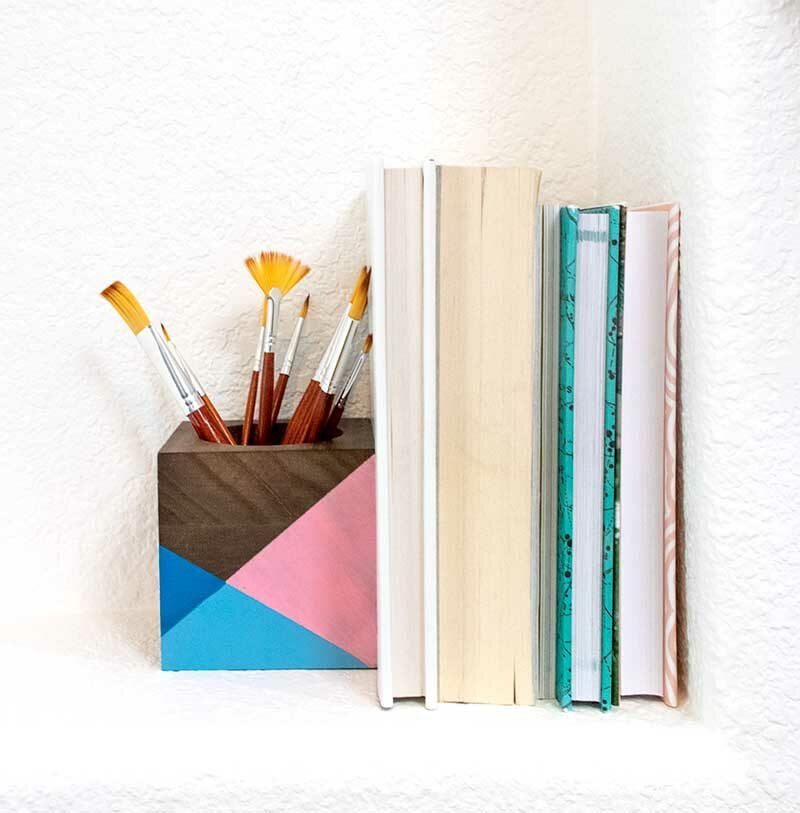 painted modern wood block book end holding up books